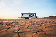 An Airstream trailer sits in the arid, desert landscape near Joshua Tree National Park, California.