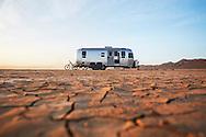 An Airstream trailer sits in the arid, desert landscape near Joshua Tree National Park, California.