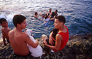 25 JULY 2002 - HAVANA, HAVANA, CUBA: Men with their dogs on the Malecon, the seaside boulevard in Havana, Cuba, July 25, 2002..PHOTO BY JACK KURTZ