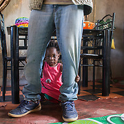 INDIVIDUAL(S) PHOTOGRAPHED: Nancy Chama. LOCATION: Ten Miles, Lusaka, Zambia. CAPTION: Nancy Chama peeks out from between the legs of her father, Albert, at their home in Ten Miles, Lusaka, Zambia. Albert completed his bricklaying training at the Build It Centre of Excellence with Build It International, a charity that trains unemployed young people in Zambia to become builders, while at the same time building vital schools and clinics in communities with little or nothing by way of resources.