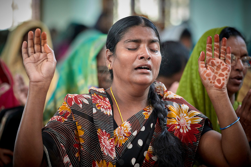 A woman prays during Sunday worship in the Centenary Methodist Church in Hyderabad, India.