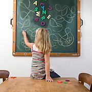 Nederland Rotterdam 12-09-2010 20100912 <br /> <br /> - MODEL RELEASED- , niet in andere context gebruiken dan in onderstaande informatie is beschreven of in keywords is aangegegeven -  Serie alfabetisme. Deze week is de week van de alfabetisering. Jong meisje van 6 jaar oud speelt met magneetletters op schoolbord en noteert uitgebreid haar eigen versie van o.a. de letter E op het schoolbord. Little girl, 6 years old, is already capable of writing some letters, in this image she is writing down her own versions of the letter E. Holland, The Netherlands, dutch, Pays Bas, Europe <br /> <br /> Foto: David Rozing
