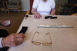 Close up of game of dominoes at day centre,