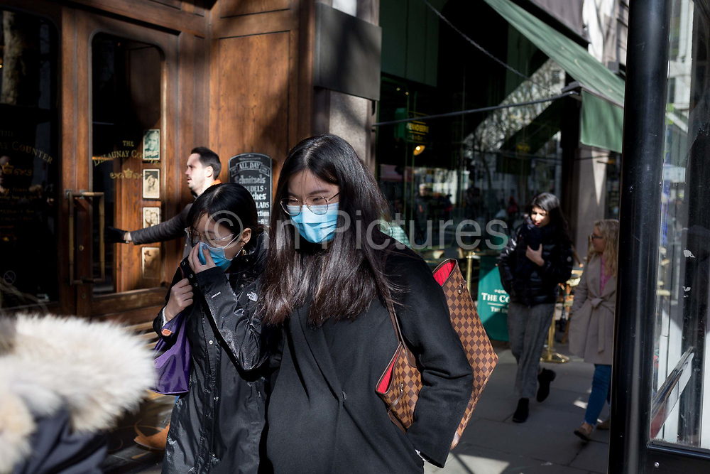 On the day that the UK Governments Chief Scientific Advisor, Sir Patrick Vallance said that the Coronavirus Covid-19 outbreak was now spreading person to person in the UK, foreign students wearing surgical masks walk along Aldwych during their lunch-hours, from nearby London School of Economics LSE, on 6th March 2020, in London, England.