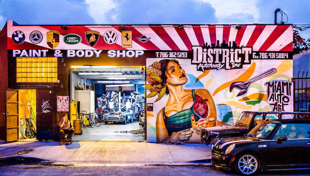 Some older industrial businesses in Wynwood, like this auto body shop, now feature surreal new murals.