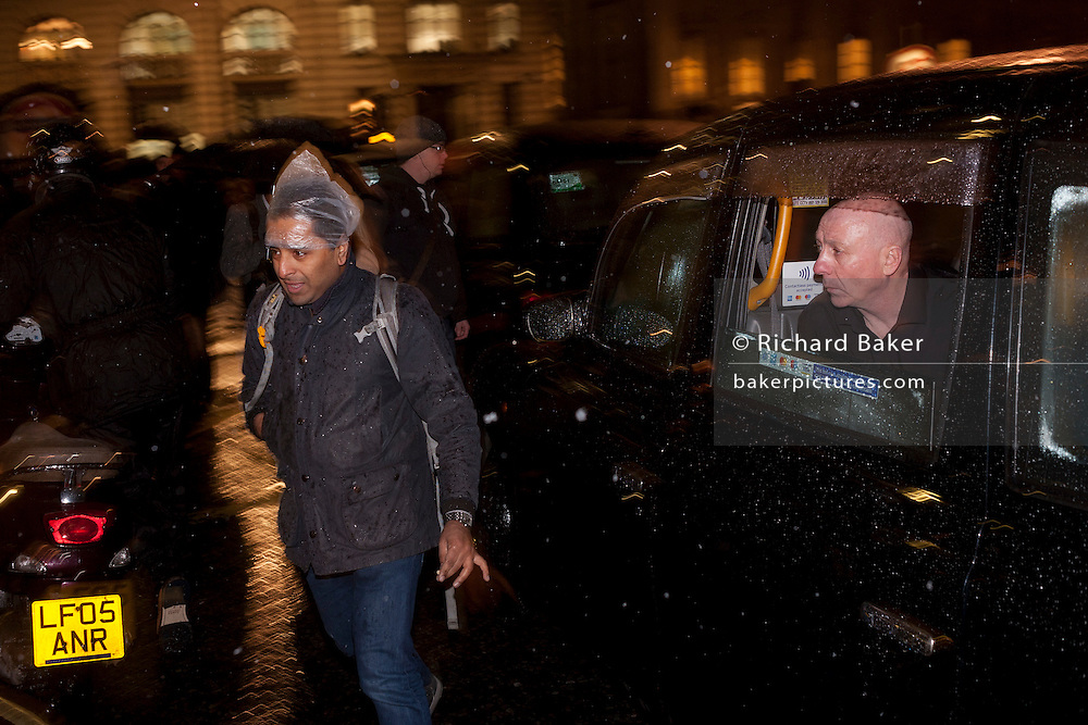 A Taxi drivers' protest gridlocks Bank junction in London's financial district with their black cabs, forcing cyclists and pedestrians to weave around the stopped vehicles during the first UK snows of the winter, on 12th January 2017, in the City of London, England. The drivers are protesting that taxis and other traffic will be banned from here, one of London's most notorious junctions in a ground-breaking road safety measure to start in April. Only cyclists and buses will be allowed to use Bank junction between the hours of 7am and 7pm after the City of London Corporation after a series of cycling deaths at this location.