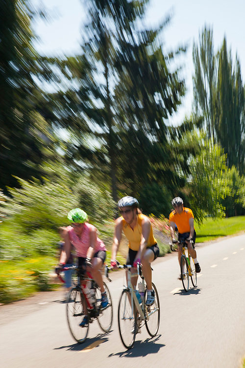 United States, Washington, Redmond, cyclists on Sammamish River Trail (blurred motion)