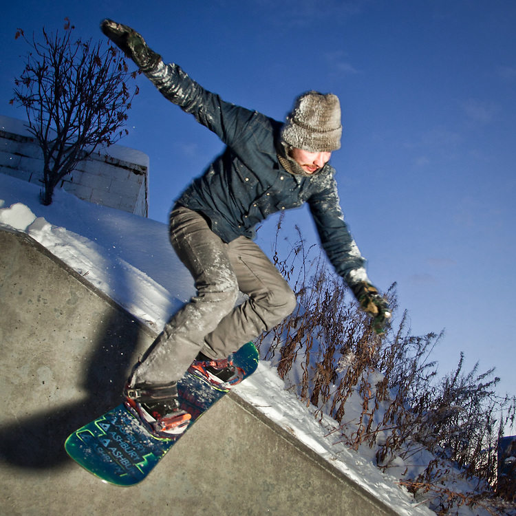 Urban snowboarder, Guss Engle, performs a Wallie Nose Glide Pretzel on the 5th Avenue Hill across from Elderberry Park, downtown Anchorage
