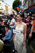 Woman in a wedding dress, dressed up as Kate walks the street looking for people called William to hopefully marry. She is rfustrated to not have found anyone yet. Street party on Battersea High Street to celebrate the Royal Wedding of Prince William and Kate Middleton, April 29th 2011. Thousands attended this one of the largest street parties in London. Embracing the diversity of the community, the theme of the party is world food, dance and music, with live coverage of the royal Wedding aired on a giant screen.