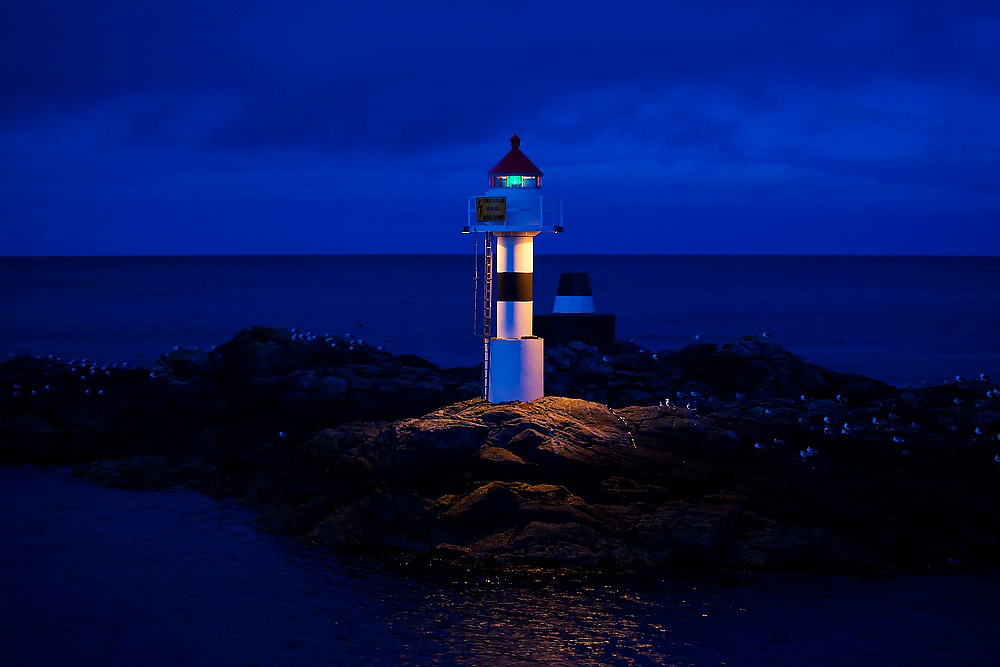 A small lighthouse on a rock at the entrance to the harbor in Sorland on Vaeroy Island, Lofoten Islands, Norway.