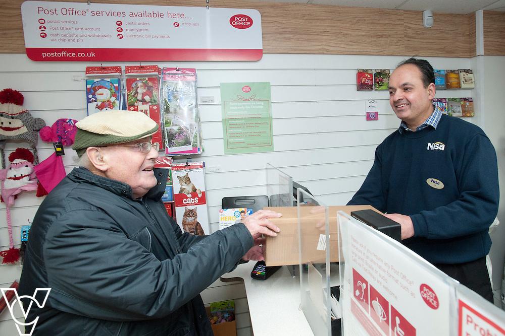 Pictured is postmaster Gurbant Dhillon serving customer Arthur Sheppard<br /> <br /> Sundown Park Post Office, Luton.<br /> Date: December 8, 2014