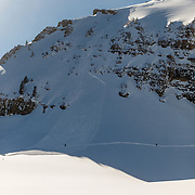 Skiers traverse across a recent avalanche runout in the Teton backcountry.