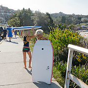The beach of Bondi on saturday. Kids with their body board.
