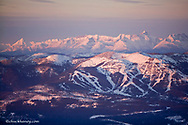 Aerial view of Big Mountain Ski Resort with peaks of Glacier National Park in winter near Whitefish Montana