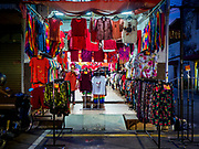 24 AUGUST 2018 - GEORGE TOWN, PENANG, MALAYSIA:  A woman hangs up clothes in her shop across the street from Chowrasta Market in central George Town. Chowrasta Market was originally built in 1890 and is the older of two traditional markets in George Town. The original building was torn down and replaced with a modern building in 1961 and has been renovated several times since.    PHOTO BY JACK KURTZ