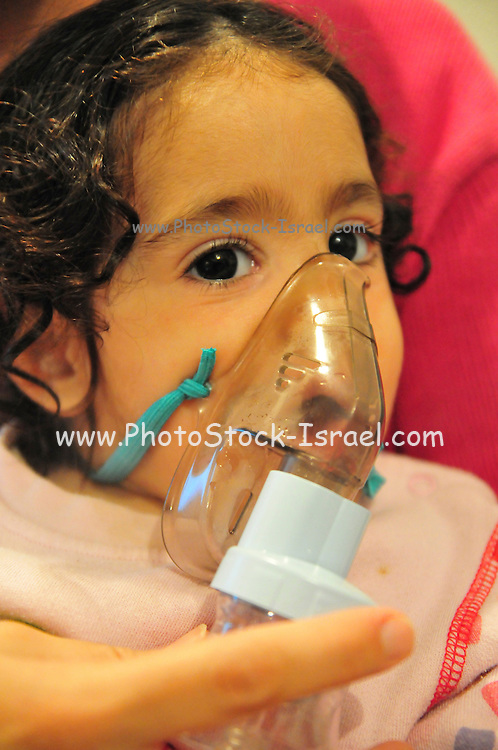 Health - young girl of 3 suffers from Asthma oxygen humidifier inhaler helps her breath - Model Release available