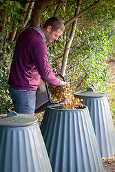 Putting leaves that have been gathered and shredded using a mover into a compost bin.