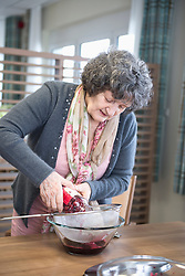 Senior woman preparing dessert in rest home