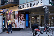 A street cleaner sweeps up and a cyclist checks his rental bike next to the closed Debenhams department store in London's Oxford Street as the second lockdown of the Coronavirus pandemic comes to a end, and a day before London enters the Tier 2 restriction when retailers will be allowed to once again re-open for the run-up to Christmas, on 1st December 2020, in London, England. 12,000 jobs are said to be at risk after financial negotiations failed the day after Topshop owner Arcadia fell into administration.