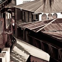 "Stone Town, Zanzibar 06 November  201<br /> View of the roof of Stone Town. Stone Town or Mji Mkongwe, in Swahili meaning ""ancient town"", is the old part of Zanzibar City, the capital of the island of Unguja, informally known as Zanzibar, part of Tanzania. The town was the centre of trade on the East African coast between Asia and Africa before the colonization of the mainland in the late 19th century after which the focus moved to Mombasa and Dar es Salaam. From 1840 to 1856, Said bin Sultan had the capital of the Omani Empire in Stone Town. The main export was spices and particularly cloves.  For many years Stone Town was a major centre for the slave trade; slaves were obtained from mainland Africa and traded with the Middle East. The town also became a base for many European explorers, particularly the Portuguese, and colonizers from the late 19th century. David Livingstone used Stone Town as his base for preparing for his final expedition in 1866. A house, now bearing his name, was lent by Sultan Seyyid Said. Immigrant communities from Oman, Persia and India lived here. <br /> Photo: Ezequiel Scagnetti"