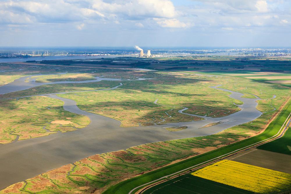 Nederland, Zeeland, Zeeuws-Vlaanderen, 09-05-2013; geulen, slikken en schorren in het Verdronken Land van Saeftinghe, getijdengebied in het oosten Zeeuws-Vlaanderen op de grens met Belgie en onderdeel van het estuarium van de Schelde. Hertogin Hedwigepolder en haven Antwerpen met kerncentrale Doel in de achtergrond. De voormalige polder is het grootste brakwatergebied van Europa en staat onder invloed van het getij. Het Verdronken Land is een natuurreservaat, in beheer bij het Zeeuws Landschap en belangrijk als broed-, overwinterings- en rustgebied voor vogels. Niet vrij toegankelijk. .The Drowned Land of Saeftinghe, tidal area in the east of Dutch Flanders on the border with Belgium. Hertogin Hedwigepolder and Antwerp port with nuclear power station Doel in the background. The former polder is the largest brackish water of Europe and because of the the tides, there are mud flats and gullies. The Drowned Land is a nature reserve, not freely accessible. It is managed by the Zeeuws Landscape and important as bird sanctuary, part of the Scheldt estuary..luchtfoto (toeslag op standard tarieven).aerial photo (additional fee required).copyright foto/photo Siebe Swart