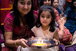 Woman and child holding out a candle in celebration of Navratri; the Hindu festival of Nine Nights,