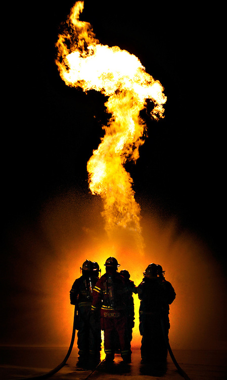 David Albers/Staff<br /> - Fire academy cadets conduct an exercise where they approach a simulated liquid propane tank fire as a team to access a shutoff valve.  As a team, the cadets use their fire hoses to divert the heat as they approach the shutoff valve at the foot of the tank.