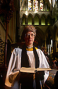 "A portrait of Britain's first lady deacon, Christine Farrington at Salisbury Cathedral. Standing in the grand architecture of the nave. Deacon is a ministry in the Christian Church that is generally associated with service of some kind, but which varies among theological and denominational traditions. In many traditions the ""diaconate"", the term for a deacon's office, is a clerical office; in others it is for laity. The word ""deacon"" is derived from the Greek word diakonos, standard ancient Greek for ""servant"", ""waiting-man"", ""minister"" or ""messenger"". Salisbury Cathedral, formally known as the Cathedral Church of the Blessed Virgin Mary, is an Anglican cathedral in Salisbury, England, and is considered one of the leading examples of Early English architecture. The main body was completed in only 38 years, from 1220 to 1258."