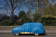A blue tarpaulin covers and protects a yellow classic Morris Minor car, parked in a south London street at the entrance to Myatts Fields Park in Camberwell on 14th April 2016. On a sunny day in the capital, the owner of this classic vintage car has protected his valuable vehicle by covering it from the UKs weather. .