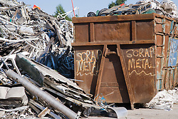 Aluminium being sorted out from scrap and rubbish prior to baling at metal recycling centre,