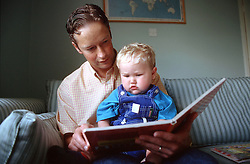 Father sitting on sofa reading story book with young son,