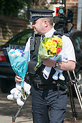 © Licensed to London News Pictures. 23/04/2014. New Malden, UK. A police officer delivers flowers to the scene. The scene in New Malden where a woman has been arrested after the discovery of three bodies of children in a house overnight. Photo credit : Stephen Simpson/LNP