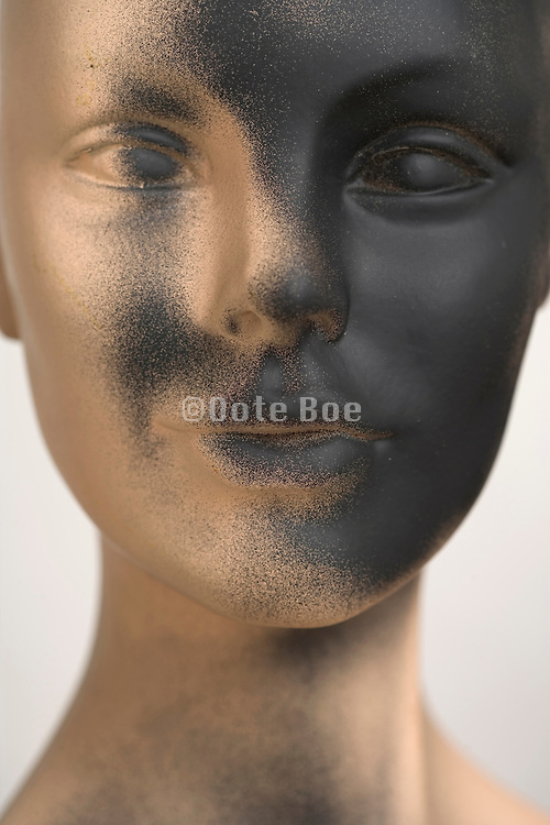 close up of a mannequin's face with a black spray painted face
