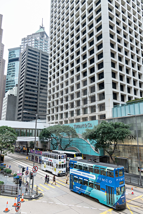 Historic double decker trams travel down Des Voeux Road in the central district of Hong Kong.