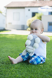Cute little baby boy biting donkey toy in the garden, Munich, Bavaria, Germany