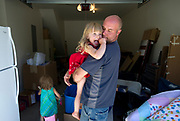 PRICE CHAMBERS / NEWS&GUIDE<br /> Jim Wolfgang picks up his daughter Isabella in the garage of their new home in Teton Village.