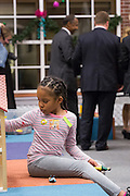 A young patient plays with her dolls unaware of retired Neurosurgeon and Republican presidential candidate Dr. Ben Carson in the background during a visit to the MUSC Children's Hospital December 22, 2015 in Charleston, South Carolina. Carson stopped by to listen to Christmas carols and greet the young patients.