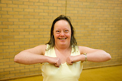 Day service user with learning disability doing arm warm up exercises in the gym,
