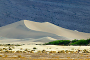 Large sand dunes form near Stovepipe Wells in Death Valley National Park, Califonria. The dunes are surrounded by mountains, though most of the sand is the result of the erosion of the Cottonwood Mountains, which lie to the north and northwest.