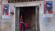 SEX INDUSTRY TOURISM. South East Asia, Cambodia, Phnom Penh. Taxi girls, prostitutes, serve foriegn tourists & Khmer, Cambodians. The sex industry is part of the fabric, servicing all classes of Cambodian society. Girls are forced into prostitution because of poverty and corruption that exists across the country. People might earn 1 to 2 $ per day, even less in rural areas, so the lure of prostitution is high. Families can sell young girls, virgins, for several hundred dollars. Cheap brothels line the streets in parts of the city centre, near railway tracks, and on the periphery. Sex for Cambodians at cheap prices in the street brothels, as low as 1 $ US, to exorbitant fees in penthouse hotel suites for the rich. Sex tourism industry attracts Western and Asian tourists typically paying 10 - 30 $ US. Expressions such as 'yam yam', eating, for a blowjob 'bam bam' for intercourse. There are 'lady-boys', youths, who use the money to pay for  sex change operations. Prostitutes spend lots of money on make-up, clothes, and mobile telephones. They live in squalor. Due to public advertising campaigns and outreach work, Aids and HIV cases have dramatically decreased, in Cambodia, since the late '90s. Condoms are encouraged, are cheap and widely available. This is seen as  a success story by medical and health authorities. There are risks as ex-prostitutes known as 'sweethearts' don't use condoms with their partners. Brothels, v & madams take their cut, but many taxi-girls work as free agents. Bars, pool halls or beer gardens have staff and taxi-girls available to service male clients, some work as barmaids or escorts. There is violence against prostitutes; gang-rape and murder by Khmer gangs. Once a girl has worked as a prostitute it is unlikely she can ever marry.///A prostitute whose apartment opens upon the street, awaits prospective clients. She says that the money pays for her educational studies..