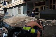 Boy sleeping on a scooter just before policemen form CRS  unit during police raid in the poor neighborhood Font Vert (Marseille). Font Vert is one of the poorest districts in the city, used as a basis for drug trafficking on a large scale. In North Marseille, drug traffic is flourishing, leading to murders among groups of competing dealers. 19 people were shot dead in drugs related killings in 2012, mainly with Kalachnikovs..... .Garçon s'est endormi sur un scooter devant es policiers anti-émeute,  au cours d'une descente de la police dans le quartier pauvre Font Vert (Marseille)..Font Vert est une des cités les plus pauvres dans la ville, utilisée comme une base pour le trafic de drogue à grande échelle. Dans les quartiers du Nord le  trafic de drogue est florissante, conduisant à des reglements de compte par des groupes de dealers concurrents.....Op scooter slapende jongen en ME-politiemannen tijdens een inval in de arme wijk Font Vert (Marseille). .Font Vert is één van de armste flatwijken in de stad, en wordt gebruikt als basis voor grootschalige drugshandel. Er vonden onlangs afrekeningen in het drugsmilieu in Font Vert plaats.