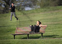 © Licensed to London News Pictures. 12/04/2020. London, UK. A woman relaxing in the sun on Primrose Hill in London on Easter Sunday, during a pandemic outbreak of the Coronavirus COVID-19 disease. The public have been told they can only leave their homes when absolutely essential, in an attempt to fight the spread of coronavirus COVID-19 disease. Photo credit: Ben Cawthra/LNP