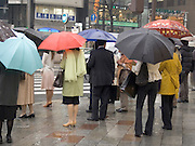 people on there way to work waiting to cross the street on a rainy day Tokyo Ginza
