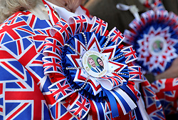 A royal fan wears a Prince Harry and Meghan Markle Union Jack rosette at Windsor Castle.