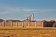 Active pump jack hear homes in Midland Texas in the Permian Basin.