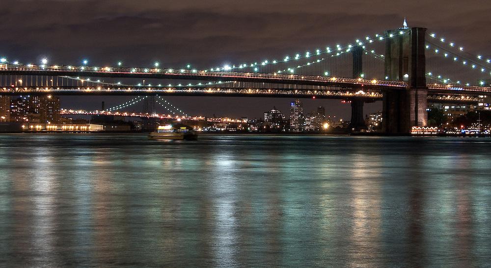 Brooklyn, Manhattan and Williamsburg bridges lit up at night shot from Pier 11 Ferry Terminal in Lower Manhattan