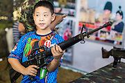 """11 JANUARY 2014 - BANGKOK, THAILAND:  A Thai boy plays with a M16 Assault Rifle during Children's Day in Bangkok. The Royal Thai Army hosted a """"Children's Day"""" event at the 2nd Cavalry King's Guard Division base in Bangkok. Children had an opportunity to look at military weapons, climb around on tanks, artillery pieces and helicopters and look at battlefield medical facilities. The Children's Day fair comes amidst political strife and concerns of a possible coup in Thailand. Earlier in the week, the Thai army announced that movements of armored vehicles through Bangkok were not in preparation of a coup, but were moving equipment into position for Children's Day.     PHOTO BY JACK KURTZ"""