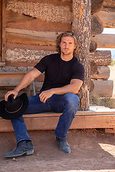 hot cowboy sitting by a rustic cabin
