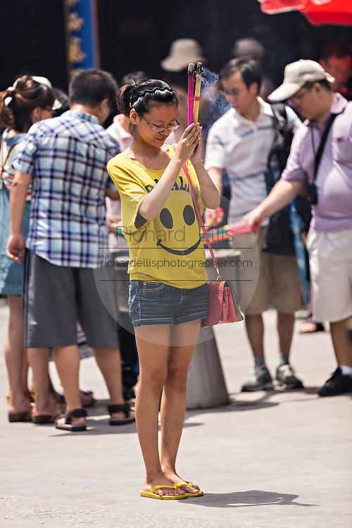 A woman prays at Chenghuang Miao or City God Temple in Yu Yuan Gardens bazaar Shanghai, China