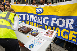 London, UK. 15 July, 2019. A cake featuring an image of Business Secretary Greg Clark is prepared by catering and cleaning staff belonging to the PCS trade union and outsourced to work at the Department for Business, Energy and Industrial Strategy (BEIS) via contractors ISS World and Aramark standing on the picket line outside the Government department after walking out on an indefinite strike for the London Living Wage, terms and conditions comparable to the civil servants they work alongside and an end to outsourcing.